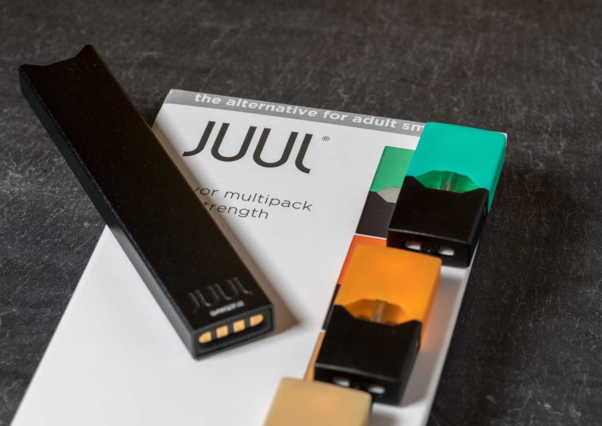 A Juul charger and assorted flavored vapor packs sit on top of an e-cigarette starter pack.