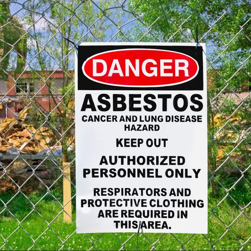 A warning sign stands outside of a construction site that is contaminated with asbestos.